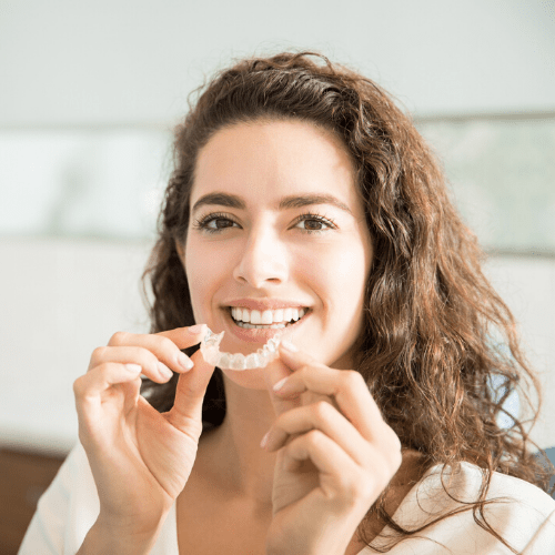 A patient holding an Invisalign aligner tray next to her mouth