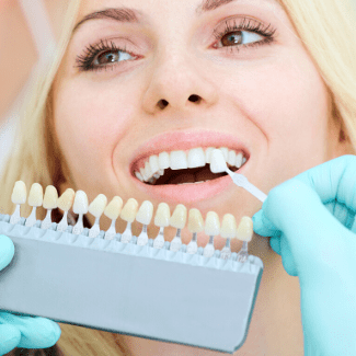 Close-up of Dr. Thompson comparing tooth colors on a patient for a teeth whitening service